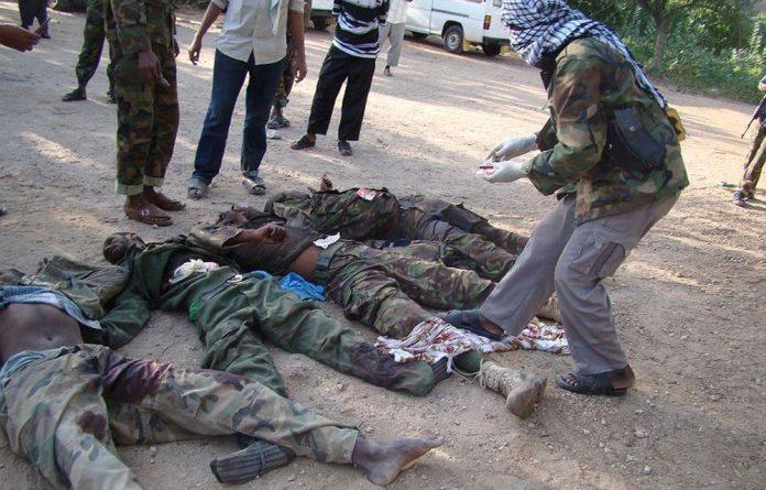 Somalia's al-Qaeda-linked al-Shabaab militants display the bodies of four 'enemy' soldiers killed in combat in Kismayo