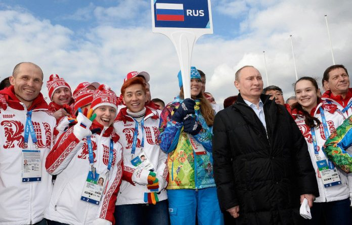 Russian President Vladimir Putin poses with athletes during a visit to the Olympic village in Sochi.