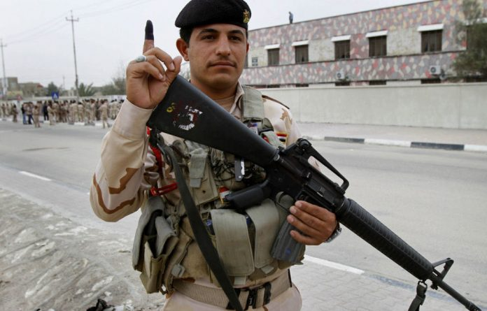 A member of the Iraqi security forces shows his ink-stained finger after voting for the provincial elections in the southern city of Basra.