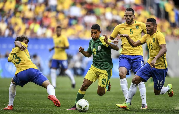 South Africa player Keagan Dolly dribbles past Brazil players Rodrigo Caio