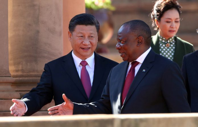 China's President Xi Jinping walks with South African President Cyril Ramaphosa before their meeting in Pretoria