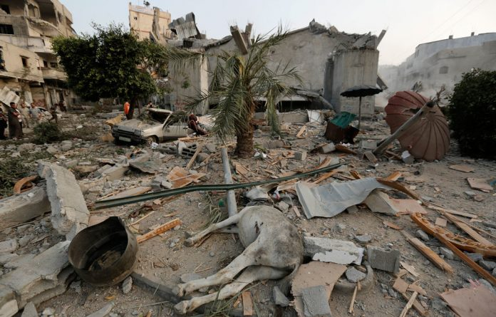 A dead donkey lies in the rubble in the northern Gaza Strip town of Jabalia on Saturday.