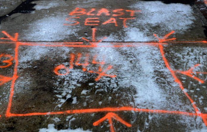 The outline of the Boston bombing blast seat on the sidewalk of Boylston Street.