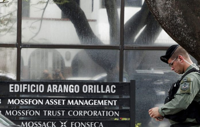 Police officers stand guard next to a company list showing the Mossack Fonseca law firm outside their office in Panama City.