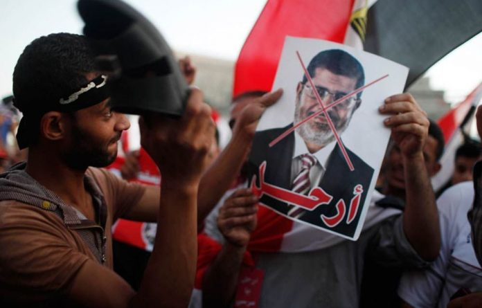A protester uses his sandal to beat a crossed-out picture of Mohamed Mursi during an anti-Morsi and anti-Muslim Brotherhood protest in Tahrir square in Cairo.