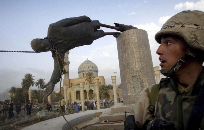 A US marine watches as a statue of Saddam Hussein falls in Baghdad after the start of the Iraq war. Future historians are likely to downsize President George W Bush as well.