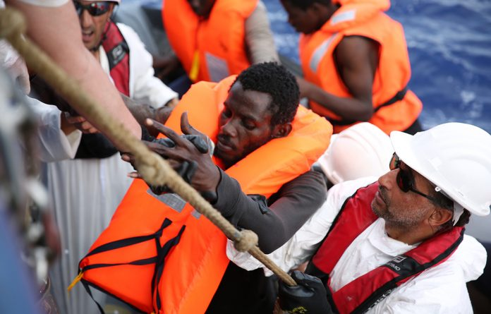 A refugee is helped onto the Dignity 1 after having been rescued from a dinghy on the Mediterranean Sea. Photo: Mohammad Ghannam/MSF