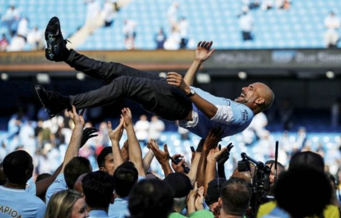 Coach Pep Guardiola is tossed in the air as Machester City celebrate winning the title