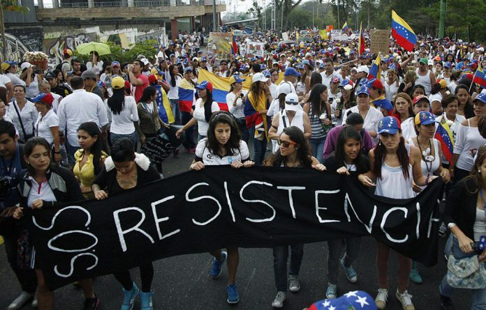 People hold a banner reading 'Resistance' during a protest against the government of Venezuelan President Nicolas Maduro in San Cristobal