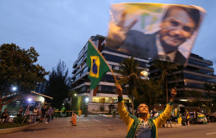 A supporter of Brazilian presidential candidate Jair Bolsonaro is seen in front of Bolsonaro's condominium at Barra da Tijuca neighbourhood in Rio de Janeiro
