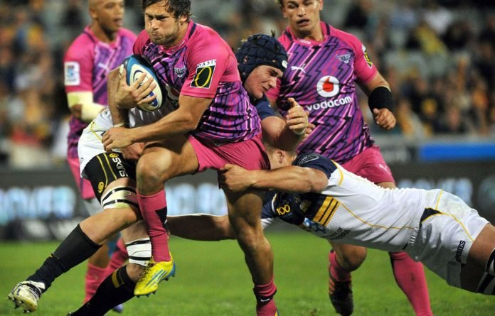 Jan Serfontein of the Bulls is tackled by Brumbies players during round seven of the rugby Super Rugby match in Canberra.