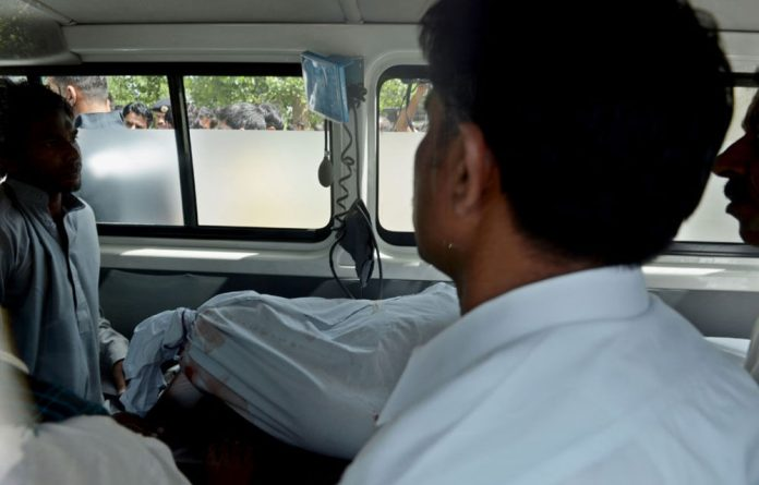 Mourners and staff of state prosecutor Chaudhry Zulfiqar sit next to his body after receiving it from hospital in Islamabad.