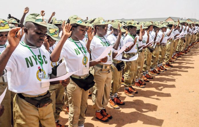 A batch of corps members take an oath of allegiance during their swearing-in ceremony in Jos