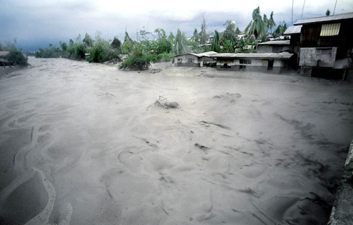 A cascading mudflow of volcanic debris from Mount Pinatubo engulfs a river in Porac