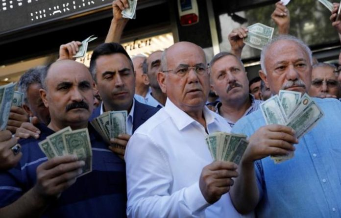 Businessmen line up in front of a currency exchange office in Ankara in response to the call of Turkish President Erdogan on Turks to sell foreign currency to support the lira.