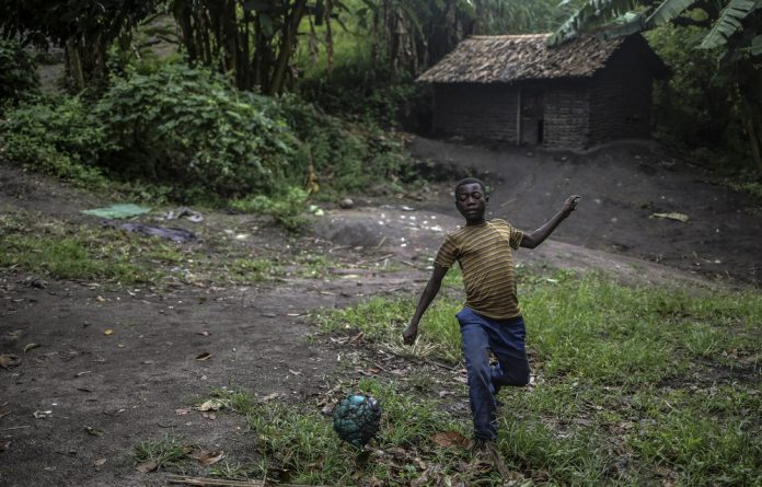 Play back: A boy kicks a football in the DRC. The pay gap between professional players is getting wider. Photo: Therese Di Campo/Reuters