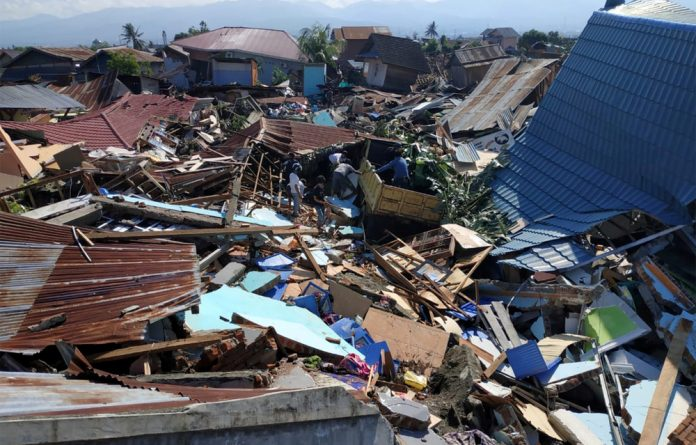 People search through debris in a residential area following an earthquake and tsunami in Palu