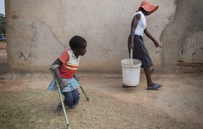 10-year-old Tanya is assisted by her neighbour Florence in the settlement where they reside in Epworth