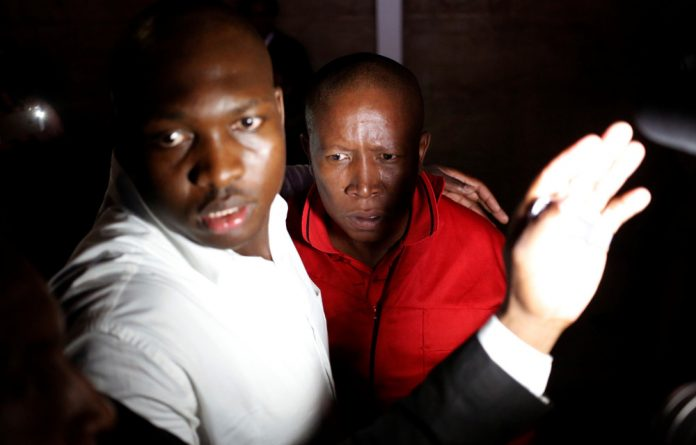 EFF leader Julius Malema is escorted out of Parliament.