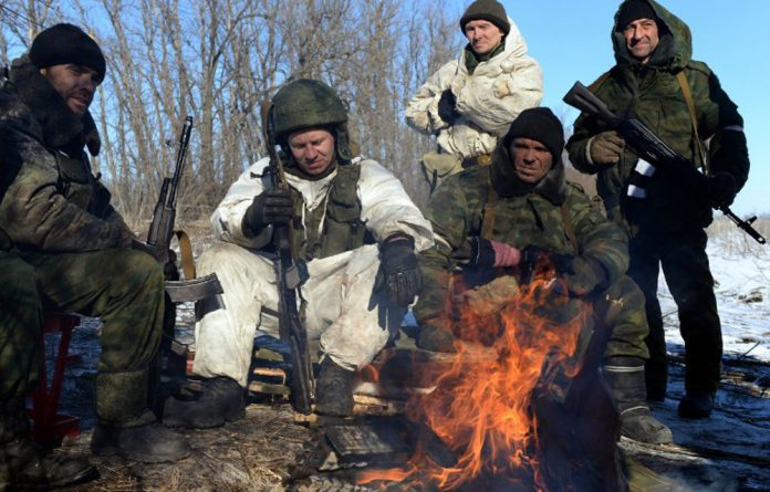 Pro-Russian rebels warm themselves by a fire during a break in fighting near the eastern Ukrainian city of Debaltseve