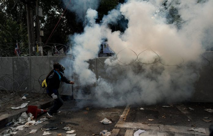 An anti-government protester throws a teargas cannister back at police outside Governement House during clashes in Bangkok on December 1.