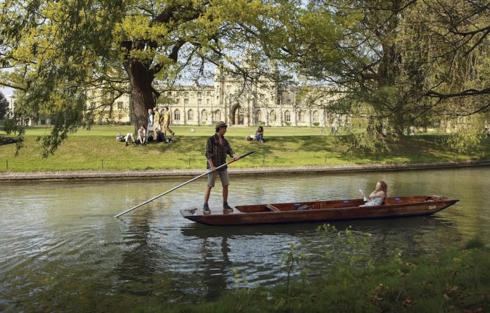 Punters along the river Cam in front of the colleges of Cambridge University