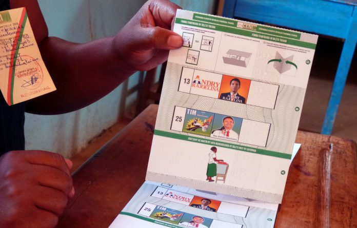 An electoral official holds the ballot paper containing the electoral details of Madagascar presidential candidates Andry Rajoelina and Marc Ravalomanana.