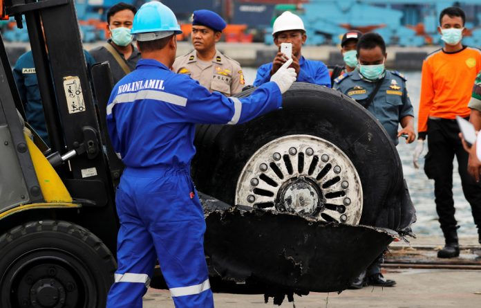A worker assists his colleague during the lift up of a damaged tyre from the Lion Air flight JT610 jet
