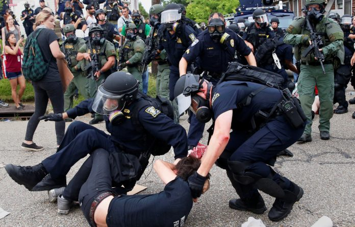 A demonstrator is detained by police during protests in Baton Rouge