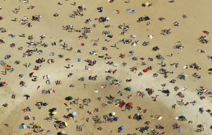 An aerial view shows people relaxing on a beach on the shores of the Silbersee lake on a hot summer day in Haltern