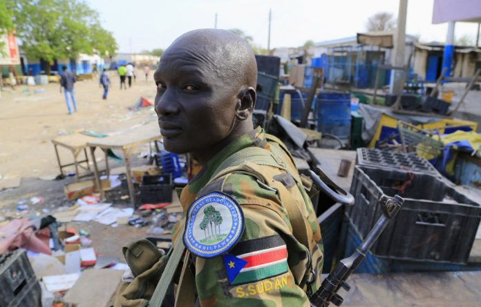 A South Sudanese army soldier stands near belongings thrown on the street of Malakal town