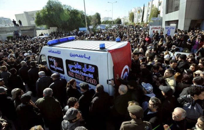 People surround an ambulance transporting the body of Tunisian opposition leader Chokri Belaid from a clinic in Tunis to the public hospital for an autopsy.