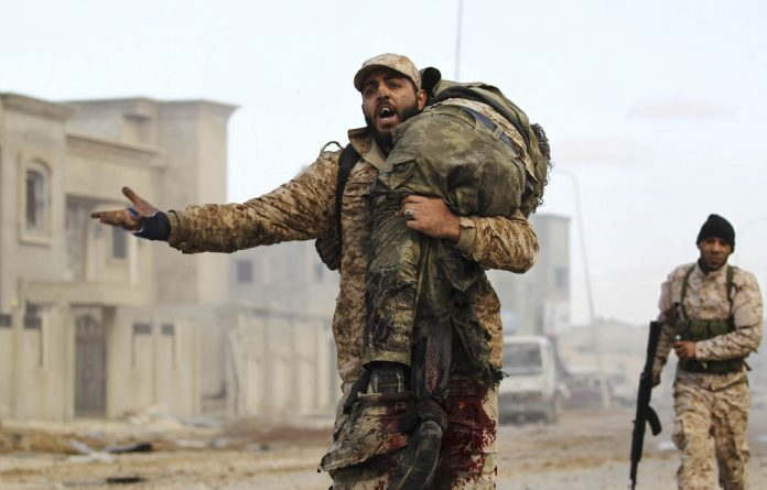 No end in sight: A member of the Libyan National Army carries an injured comrade during fighting against jihadists in Qanfudah