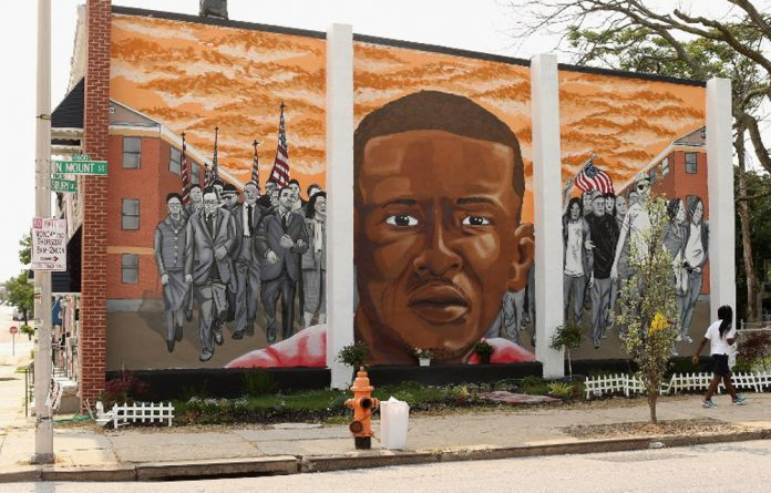 A mural memorialising Baltimore resident Freddie Gray is painted on the wall near the place where he was tackled and arrested by police.