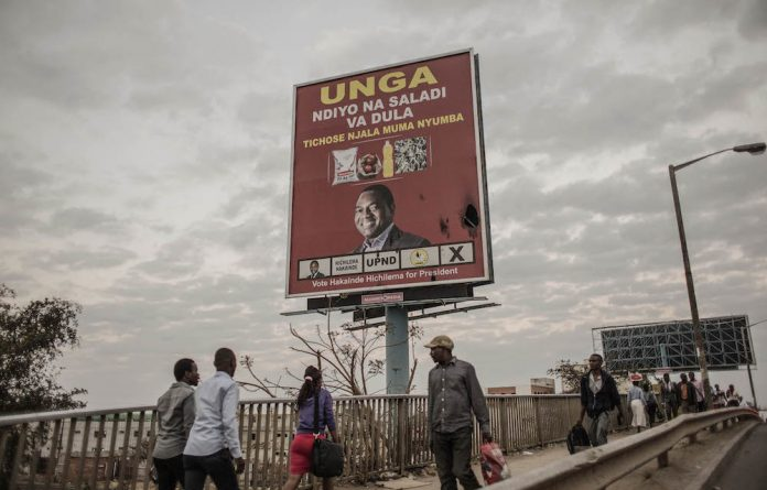 People walk by a presidential campaign billboard of United Party for National Development