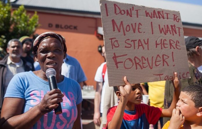 Bromwell Street resident Jienen Fleurs addresses protesters at The Old Biscuit Mill on Saturday morning.