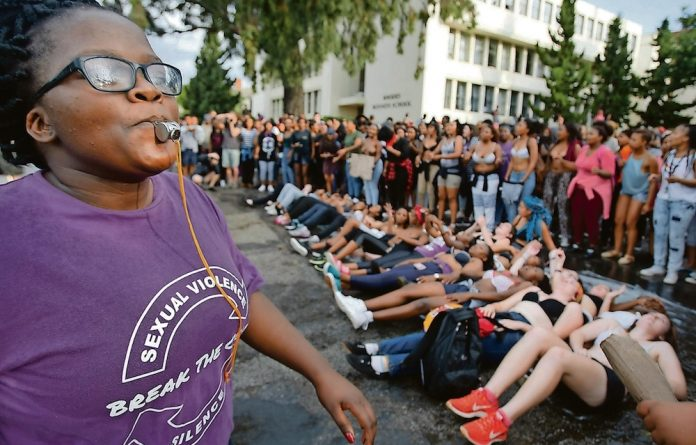 A Rhodes University student blows a whistle during a protest against sexual violence in the institution.