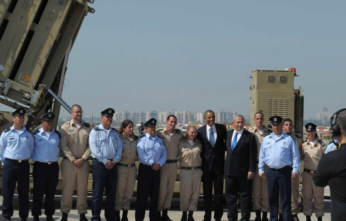 President Barack Obama and Israel's Prime Minister Benjamin Netanyahu pose with military personnel next to a battery of Iron Dome.