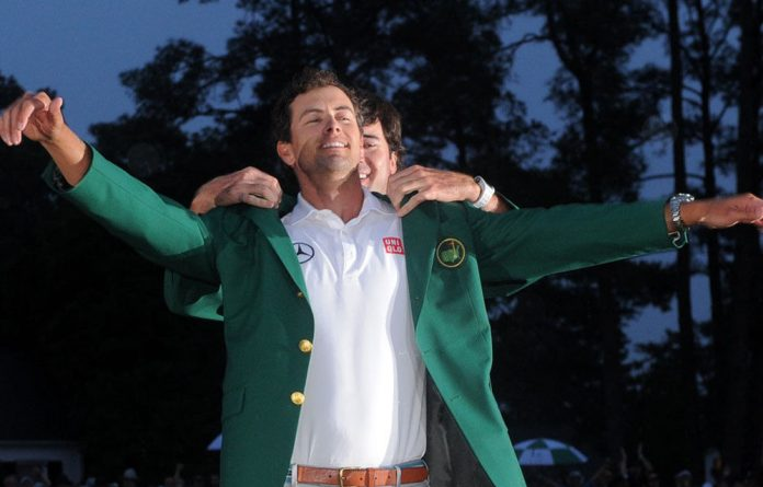 Bubba Watson of the US presents Adam Scott with a green jacket during the Green Jacket Ceremony at 77th Masters golf tournament at Augusta National Golf Club.