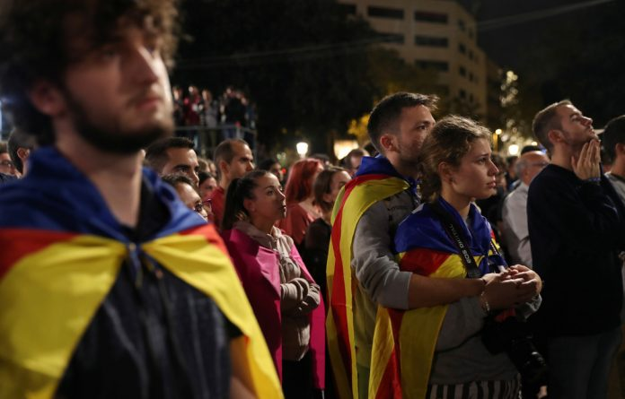 People react as they listen to Catalan president Carles Puigdemont during a gathering at Plaza Catalunya after voting ended for the banned independence referendum