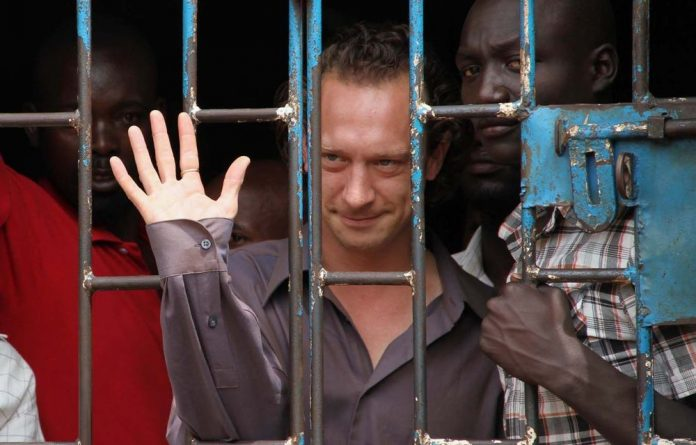 British theatre producer David Cecil waving from a court cell at the Makindye Court in Kampala.
