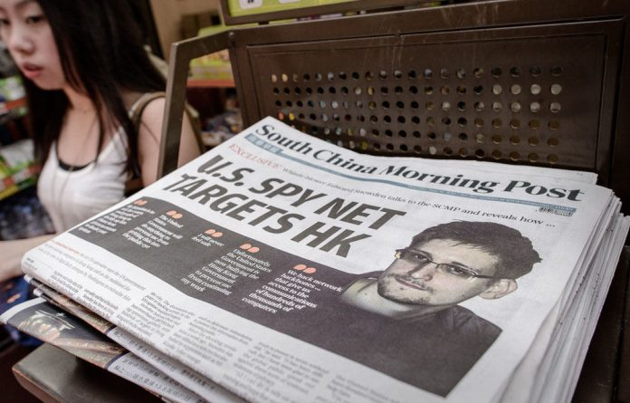 A woman walks past an edition of the South China Morning Post carrying the story of former US spy Edward Snowden on its front page in Hong Kong on June 13.
