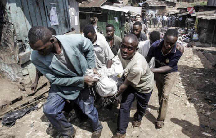 Slum dwellers carry the body of a suspected Mungiki gang member in June 2007 in Nairobi's Mathare slum