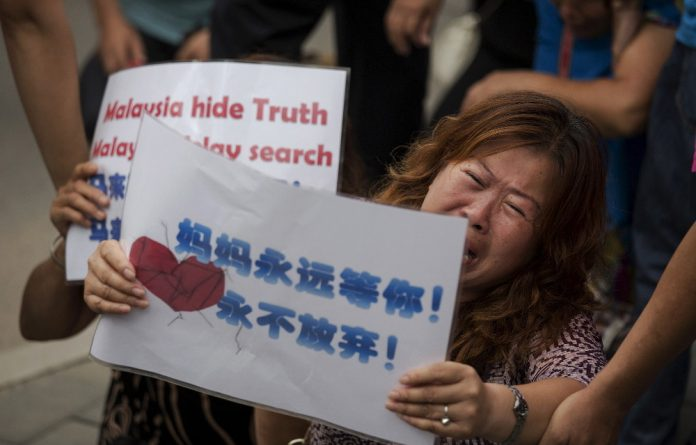 People whose relatives were aboard flight MH370 kneel and cry in front of the media near the Malaysian embassy in Beijing after they scuffled with police who stopped them from entering a road leading to the embassy.