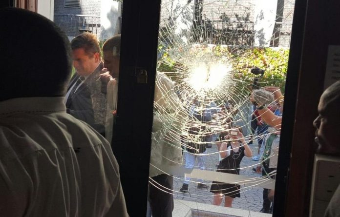 Protection officers closed a glass door in Parliament which was later shattered after objects were hurled.