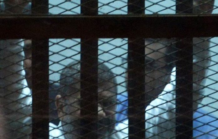 Egypt's former president Mohammed Morsi gestures from the defendent's cage during his trial.