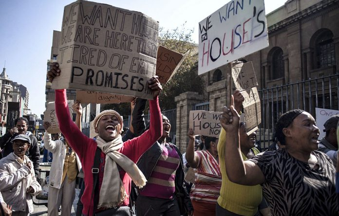 Eldorado Park residents illegally occupying vacant land demand houses from government at a protest outside the Johannesburg high court on May 12 2015.