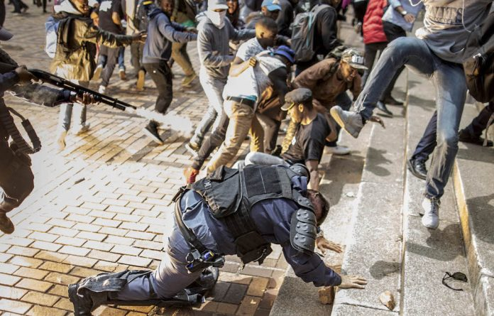 Scenes of chaos: During a clash between students and police at the University of the Witwatersrand on Tuesday an officer falls and a colleague fires rubber bullets at fleeing students.