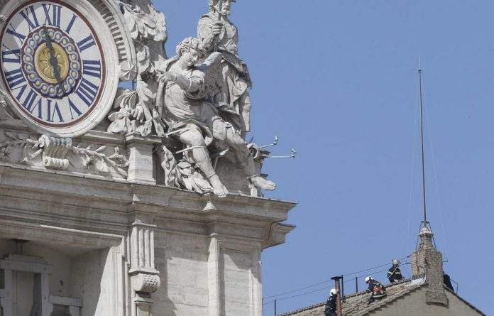 Firefighters place the chimney on the roof of the Sistine Chapel on Saturday