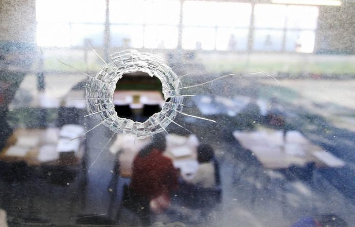 A Grade 1 classroom is seen through a bullet hole in one of the windows at Sonderend Primary School in Manenberg